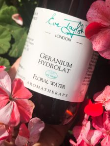 A bottle of Eve Taylor's Geranium hydrolat nestled in geraniums
